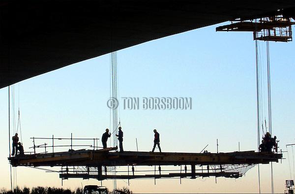VIANEN 0 Boven de Lek tussen Vianen en Nieuwegein is de laatste betonbekisting van de nieuwe, derde Lekbrug naar beneden getakeld. De 532 meter lange derde Lekbrug is gebouwd met hulp van uitbouwbruggen waarbij vanaf een brugpijler wekelijks een stuk betonweg van 3,6 meter werd aangebouwd. De komende weken worden het wegdek met interne kabels stevig aangetrokken, worden hulppijlers verwijderd, en gaat de afbouw van de brug van start. De 29 meter brede brug bevat 22.000m3 beton en ruim 3000 ton staal, weegt ongeveer 33.000 ton en kost twintig miljoen euro. COPYRIGHT TON BORSBOOM