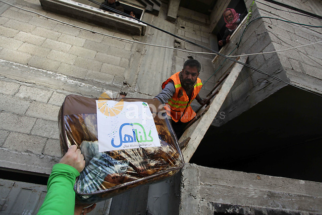 Palestinian rescuer workers deliver aids to the residents in Al Sheikh Redwan area that was flooded in Gaza City, 18 December 2013. Four days of torrential rains in Gaza Strip killed two people and forced the evacuation of more than 5,000 residents from flooded homes, some accessible only by boat, officials said. Photo by Ashraf Amra