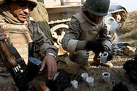 Iraqi tankers from the 1st company, 1st armour battalion of the 1st mechanized Iraqi Army Brigade prepare their tea seeking cover in back of their tank   while conducting  patrols, check points and observation posts on code name route Michigan, the main road of Ramadi in the week during the national election on TUE Dec 13 2005 in Ramadi, Iraq. 1st company is part of the first armor battalion of the New Iraqi Army. it has started its training in January 2005. after 50 days their 35 russian and chinese built T 55 tanks begun conducting operations under the guidance of a US military adivisor team. in April 2005 they patrolled in the Abu Ghraib area concluding their first significant mission. While these old tanks are rolling on the ramadi streets more modern T72s are getting ready to become fully operational in Taji, their main base. the Iraqi army wanted to show their power in ramadi during the Dec 15 elections displaying their new armour company. but like all the other Iraqi forces they are not going to secure the polling sites, staying in the rear with the rest of the iraqi and coalition forces. T 55s are very old tanks. production begun in the late 50s to the late 70s. athough obsolete many countries still use the T55 as their main heavy armoured combat vehicle. slow, heavvy and with very little room for the crew it suffers from many mechanical problems constantly challenging the iraqi mechanics and engineers.
