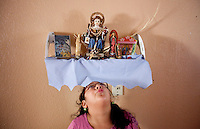 leaving0627 Vanessa Sanchez, 10, (CQ) looks up at a shrine in her family's kitchen holding a figure of Santo Niño de Atoche. The family carried the figure of the saint in the front seat of their truck across country. (Pat Shannahan/ The Arizona Republic)