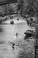 Båtar och lövträd vid Pålsundskanalen mellan Södermalm och Långholmen i Stockholm i svartvitt