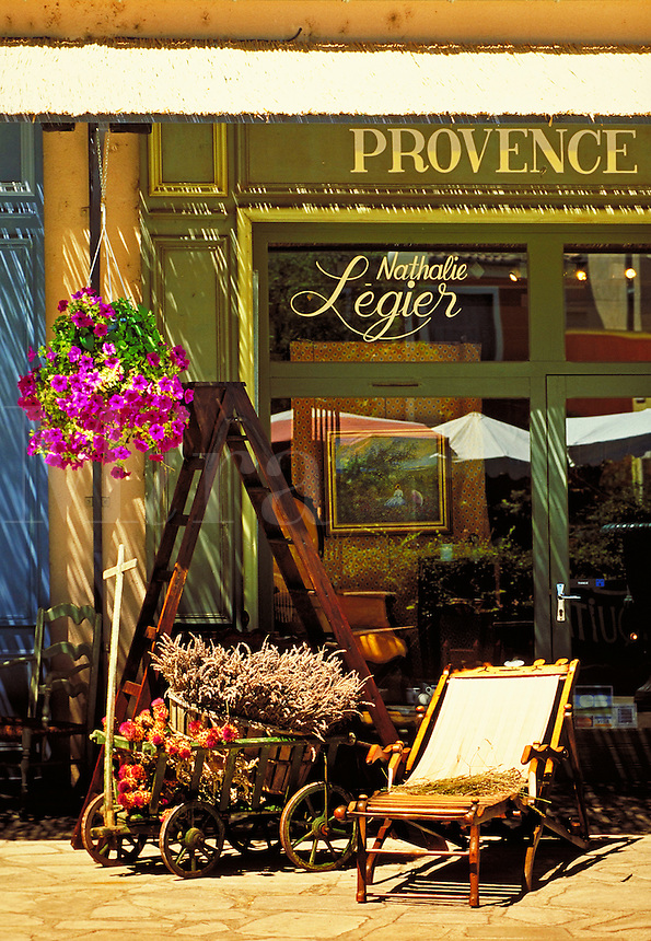 Wooden chaise, old farmer's cart with plants and wooden ladder outside Nathalie Begier's shop. Flowerpot hangs from awning. Painting and other furnishings seen in window. L'Isle sur, la Sorgue Provence France.