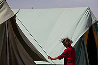 Tunisie RasDjir Camp UNHCR de refugies libyens a la frontiere entre Tunisie et Libye ....Tunisia Rasdjir UNHCR refugees camp  Tunisian and Libyan border   campo profughi frontiera libica Bambina con maglia rossa in mezzo alle tende  Red girl between tents
