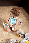 13 month old baby girl at home playing with stacking nesting boxes putting toy vehicle inside a box concept inside of vertical