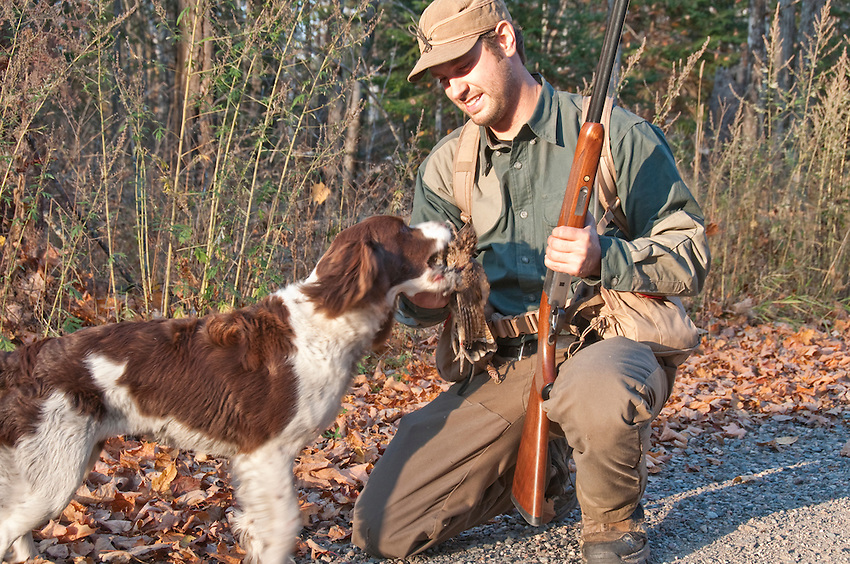 An upland bird hunter and his springer spaniel with a ruffed grouse.