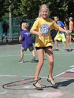 NWA Democrat-Gazette/DAVID GOTTSCHALK Lily Nelms, 9, spins a plastic hoop Friday, August 3, 2018, with her leg during the city of Fayetteville's Parks and Recreation Department Be Active! Camp Wilson at Wilson Park in Fayetteville. Camp Wilson II is scheduled for next week and for campers five through 15 and will feature sports and recreational activities.
