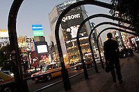 A male office worker or salaryman walks under some arches near Hachiko crossing in Shibuya, Tokyo, Japan. January 21st 2011
