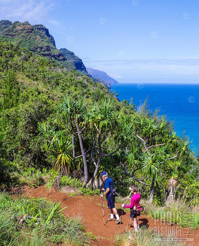 An older couple hikes the Kalalau Trail near Hanakapi'ai Beach on Kaua'i.