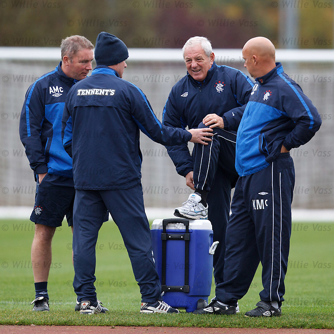 Walter Smith grimacing with a sore knee after limping onto the training ground as Ian Durrant checks it out