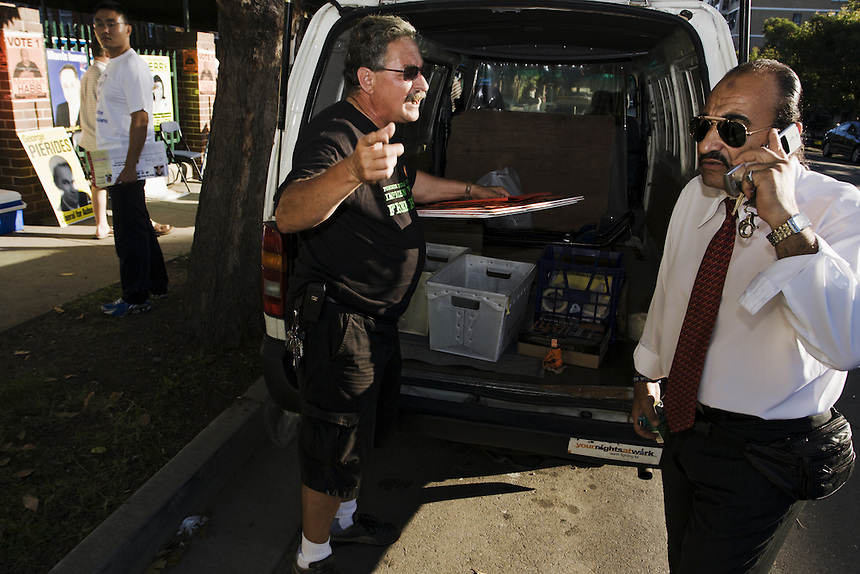 Habib and campaign manager Raul Bassi (C) discuss plans for election day outside a polling booth in Auburn, western Sydney, March 25 2007.