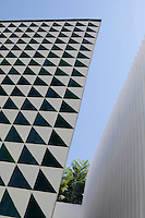 The facade of the building has been clad in black and white ceramic tiles arranged in a geometric pattern