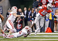 Ohio State Buckeyes quarterback Cardale Jones (12) gets taken down by Wisconsin Badgers cornerback Derrick Tindal (25) during the 1st quarter in the 2014 Big Ten Football Championship Game at Lucas Oil Stadium in Indianapolis, Ind. on December 6, 2014.  (Dispatch photo by Kyle Robertson)