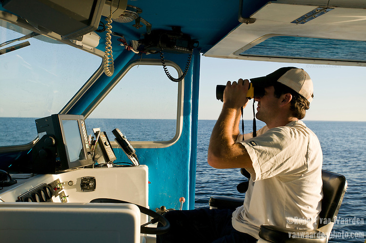 A fisherman scans the water with binoculars looking for Blue Fin Tuna. Gulf of St. Lawrence near North Rustico, Prince Edward Island, Canada.