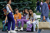 Hungary. Group of brightly dressed smiling teenage girls sitting on a park bench in a park.