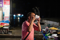 A man eats noodles and jiaozi at Xie Guang Rong's (in rainbow shirt) food stand outside the B District Middle Gate of Chongqing University in the Shapingba district of Chongqing, China. Xie Guang Rong has run the stand, which serves tu dou ni, jiaozi, and other small snacks, for 11 years. They chose the location directly outside the university gate because it's such a high traffic areas. She said that the stand is popular with students because prices are low and the portions she serves are big. A large helping of tu dou ni, for instance, costs 3RMB. She and her husband rent the stall space from the surrounding community.