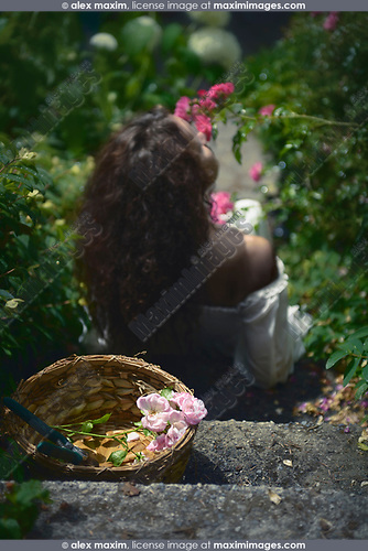 Romantic rear view portrait of a young woman smelling roses in a garden