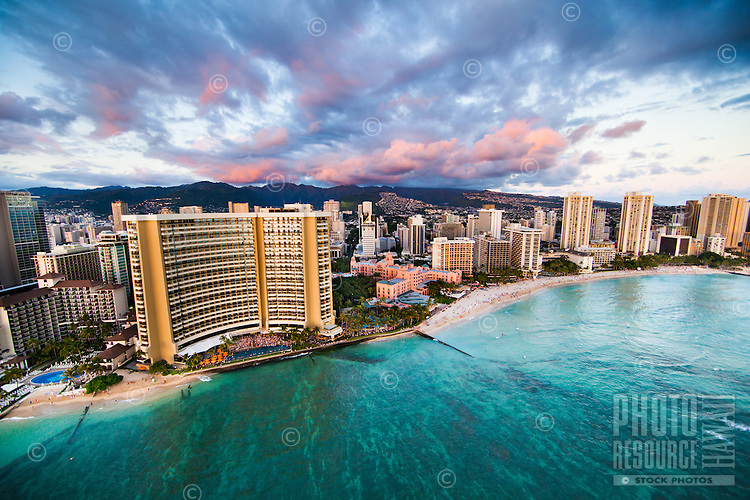 An aerial perspective O'ahu's Waikiki shoreline, with the Sheraton and the Royal Hawaiian at center and the Hyatt on the right; in the distance, pink clouds grace the top of the Ko'olau Range.