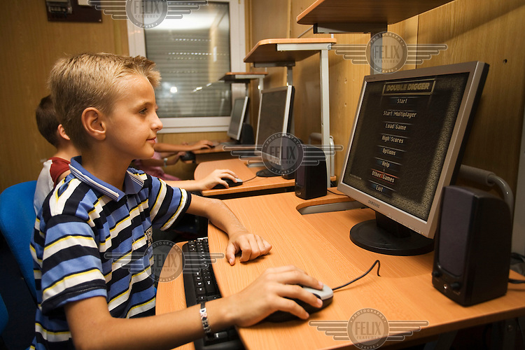 A boy plays a computer game in an internet cafe in the mixed Serb and Albanian community of Kodra e Minatoreve/Mikronaselje.