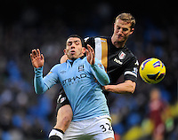 Carlos Tevez of Manchester City challenged by Brede Hangeland of Fulham - Barclays Premier League - Manchester City vs Fulham - Etihad Stadium - Manchester - 13/01/13 - Picture Simon Bellis/Sportimage .Manchester 19/1/2013 .Football Calcio 2012/2013 Premier League.Manchester City Vs Fulham .Foto Insidefoto .ITALY ONLY