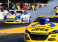 Jul. 25, 2014; Sonoma, CA, USA; NHRA pro stock driver Allen Johnson (left) does a burnout alongside teammate Jeg Coughlin Jr during qualifying for the Sonoma Nationals at Sonoma Raceway. Mandatory Credit: Mark J. Rebilas-