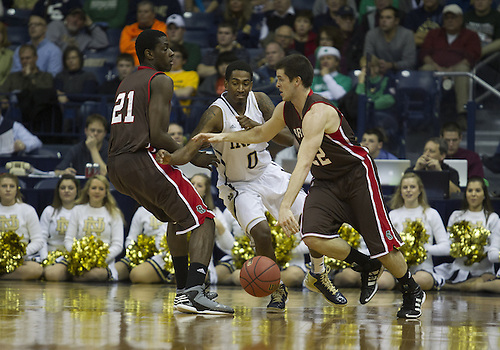 December 08, 2012:  Brown guard Sean McGonagill (22) dribbles the ball around a pick by forward Cedric Kuakumensah (21) as Notre Dame guard Eric Atkins (0) defends during NCAA Basketball game action between the Notre Dame Fighting Irish and the Brown Bears at Purcell Pavilion at the Joyce Center in South Bend, Indiana.  Notre Dame defeated Brown 84-57.