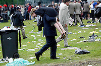 Melbourne Cup at Flemington.  Horse racing fan carries his partner across the trash-strewn lawn after a long day.