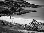 Two figures walking along a deserted beach with a rocky headland and derelict boat