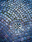 Drain cover in a cobble street, Ravenna, Italy