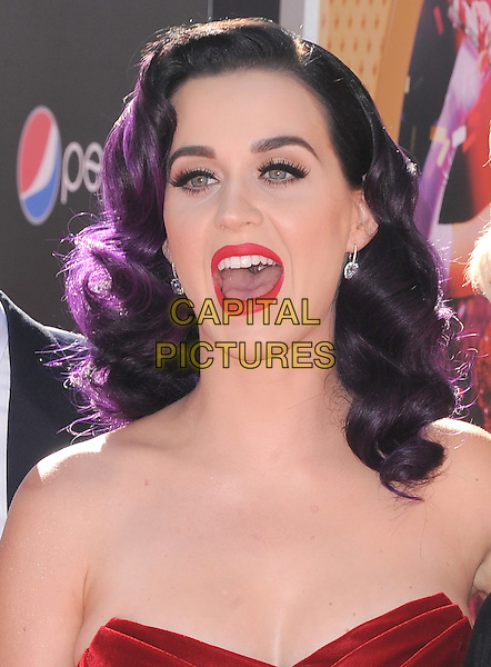 "Katy Perry.""Katy Perry: Part Of Me"" Los Angeles Premiere held at Grauman's Chinese Theatre, Hollywood, California, USA..June 26th, 2012.headshot portrait red strapless velvet dyed purple hair lipstick mouth open                                     .CAP/RKE/DVS.©DVS/RockinExposures/Capital Pictures."