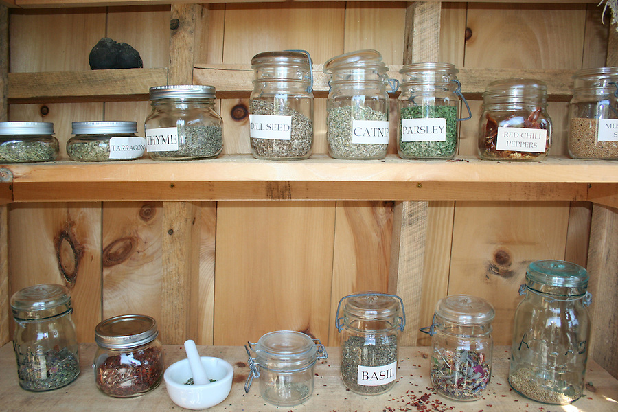 Dried herbs in bunches and jars for culinary and spa use