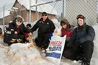 Dog drop coordinators in McGrath pose for a photo with veterinarian Turner Lewis during Iditarod 2009