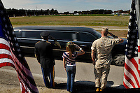 Hillsborough, Plant City, Fl. 1/20/2010- FALLEN SOLDIER RETURNS-  From left, Isreal Rivera, a vetran serving 30 years in the Army, Jaydin Hathaway, 10, and her father Jason Hathaway salute as the the funeral procession for U.S. Army SPC David A. Croft, Jr. makes its way along Turkey Creek Rd. just south of Hwy 60 as  makes its way from MacDill AFB to Haught Funeral Home in Plant City , Fla. on Wednesday, January 20, 2010. FALLEN SOLDIER RETURNS 05 OF 12 IMAGES STAFF MICHAEL SPOONEYBARGER.