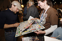 Thursday February 28, 2013  Veteran musher Jason Mackey signs an Iditarod Monopoly game for a fan at the musher drawing banquet held at the Dena'ina Convention Center in Anchorage two days prior to the start of Iditarod 2013...Photo (C) Jeff Schultz/IditarodPhotos.com  Do not reproduce without permission.