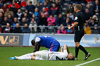 Joe Rodon of Swansea City (FRONT) and Toto Nsiala of Ipswich Town are injured on the ground next to referee Oliver Langford during the Sky Bet Championship match between Swansea City and Ipswich Town at the Liberty Stadium, Swansea, Wales, UK. Saturday 06 October 2018