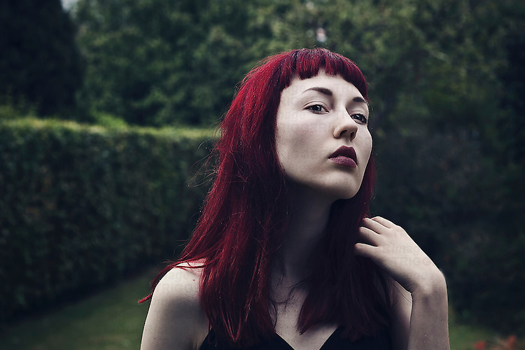 Portrait of a young female with long red hair and pale skin looking away, with garden background.