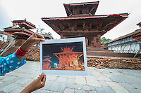Nepal, Kathmandu, earthquake damage at Kathmandu Durbar Square. Woman holding my photo of how the temples looked previously.