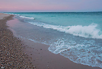 The Lake Michigan water, a teal green in overcast late light contrasts against a pink twilight sky