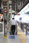 Osaka, JP - January 21, 2015 : A cleaner pushes a trash container at the trains platform in Shin Osaka station. (Photo by Rodrigo Reyes Marin/AFLO)