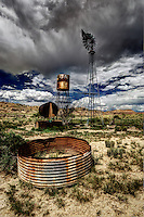An old abandoned stock tank, water tank, and windmill under a stormy sky near Torreon Wash and the Empedrado Wilderness Study Area. in northwestern New Mexico.