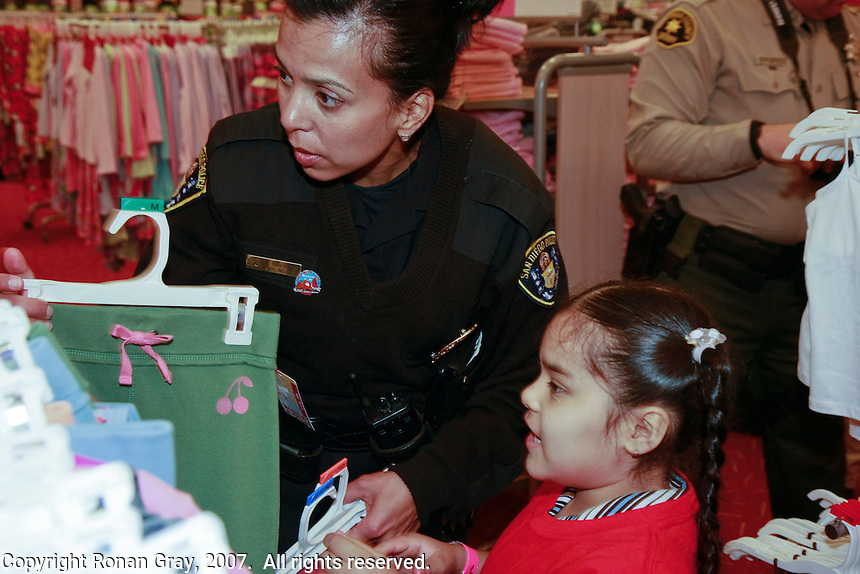 Detective Kika Navarro of San Diego's Central Division helps a child choose clothing during the Shop-With-a-Cop event at the Sports Arena Target store in San Diego on December 1, 2007.  Some of the children rose well before dawn in order to be ready for the fleet of buses that collected them from every corner of the county.  The buses took them to SeaWorld where they were paired up with an officer for the event.  After breakfast they made their way to the Target store in a huge, convoy of more than three hundred police vehicles with sirens blaring, lights flashing and Santa waving from a police helicopter hovering above them.  Each child had a $100 gift card to spend and many of them resisted the temptation to buy toys and choose instead to get clothes for themselves, their siblings or parents.