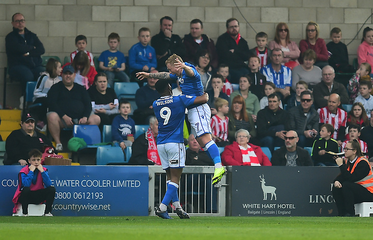 Macclesfield Town's Scott Wilson, left, celebrates scoring the opening goal<br /> <br /> Photographer Andrew Vaughan/CameraSport<br /> <br /> The EFL Sky Bet League Two - Lincoln City v Macclesfield Town - Saturday 30th March 2019 - Sincil Bank - Lincoln<br /> <br /> World Copyright © 2019 CameraSport. All rights reserved. 43 Linden Ave. Countesthorpe. Leicester. England. LE8 5PG - Tel: +44 (0) 116 277 4147 - admin@camerasport.com - www.camerasport.com