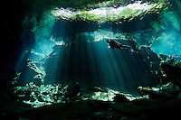 RX0630-D. scuba diver (model released) swims into a curtain of light shining down through the opening to a cenote, the entranceway to caverns and tunnels waiting to be explored. Riviera Maya, Yucatan Peninsula, Mexico.<br /> Photo Copyright &copy; Brandon Cole. All rights reserved worldwide.  www.brandoncole.com