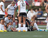 Injured Portland Thorns FC forward Alex Morgan (13) receives moral support from teammates.. In a National Women's Soccer League (NWSL) match, Boston Breakers (blue) defeated Portland Thorns FC (white/black), 2-1, at Dilboy Stadium on August 7, 2013.
