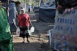 A woman carries water through a camp in Managua of some 3,000 former banana workers who have been poisoned by Nemagon (dibromochloropropane). Camped out across the street from the Nicaraguan National Assembly, the workers are pressuring the government to provide health care and support their legal actions against US companies which manufactured and used the pesticide. Nemagon is considered a risk factor for cancer, kidney failure, acute respiratory disease, heart attack, sterility, muscular atrophy, skin complaints, and other health problems. The tall building in the rear is the National Assembly.