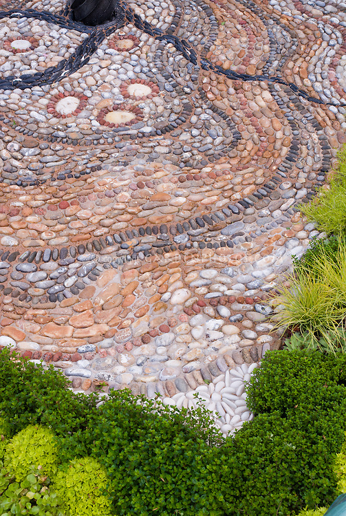 Crazy paving patio stones pebbles mosaic pattern laid flat and on edge hardscaping, with plants groundcovers Sedum, herb thyme Thymus, Carex ornamental grass, yellow and green foliage leaf colors theme