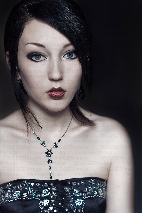 Portrait of a young woman with black hair blue eyes and pale skin wearing a black embelished corset looking into the camera with simple background.