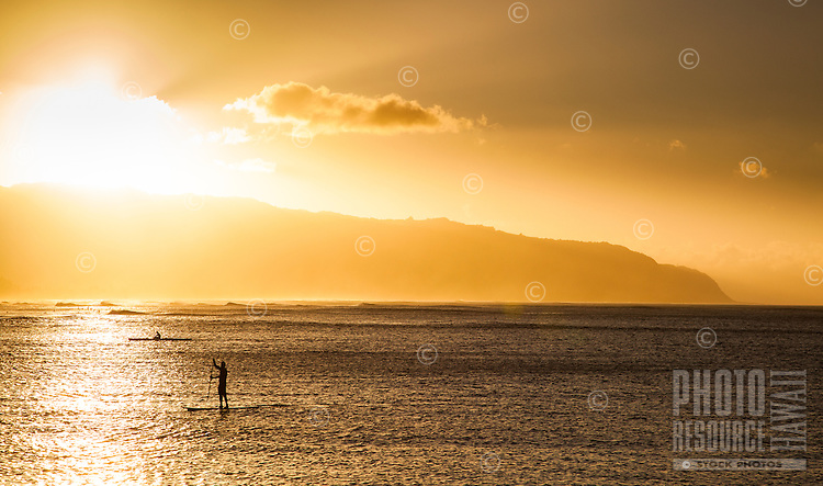 A standup paddler and kayaker at sunset, with Ka'ena Point in the background, O'ahu.