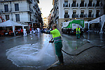Two cleaning service workers clean the streets before the second run of the bull of the San Fermin Festival, on July 12, 2012, in Pamplona, northern Spain. The festival is a symbol of Spanish culture that attracts thousands of tourists to watch the bull runs despite heavy condemnation from animal rights groups . (c) Pedro ARMESTRE