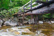 Pemigewasset Wilderness - High waters from flash floods from Tropical Storm Irene in 2011 cause peeling to the bottom of a footbridge, which crosses the East Branch of the Pemigewasset River along the Thoreau Falls Trail at North Fork Junction in Lincoln, New Hampshire USA. The bridge is supported by two large logs and they look to have received some damage. This tropical storm caused destruction along the East coast of the United States and the White Mountain National Forest of New Hampshire was officially closed during the storm.