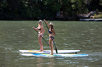 Summertime is hot in Austin. Two athletic fit females on stand up paddle board exercise on Lake Travis in Austin, Texas